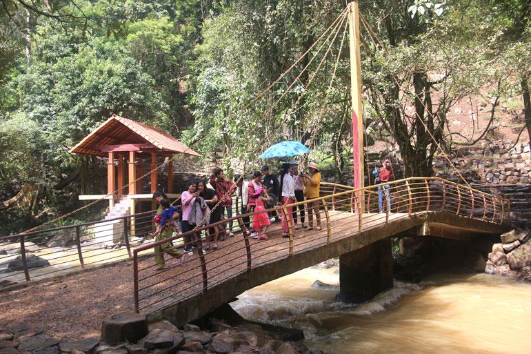 Du khách chụp ảnh lưu niệm tại cầu ở khu vực dưới thác.