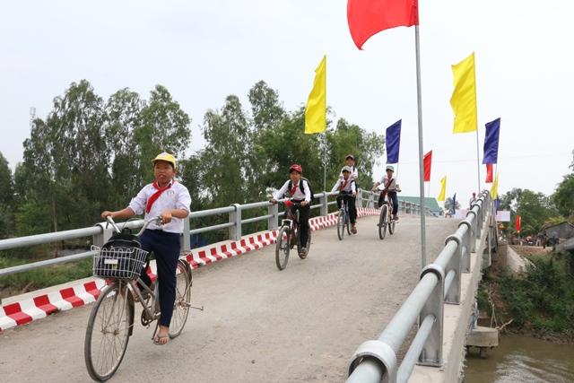 Các em học sinh vui mừng, phấn khởi đi qua cây cầu mới Nam Hang. Ảnh: Thùy Dung