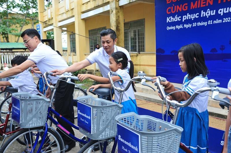 Ông Nguyễn Hồng Thành - Giám đốc Khu vực Bắc Trung Bộ và ông Nguyễn Quang Tâm - Giám đốc Chi nhánh Quảng Ngãi tặng xe đạp cho các em học sinh trường Tiểu học Bình Minh (Quảng Ngãi)