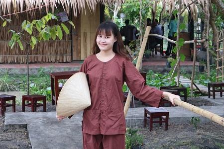 Du khách tạo dáng với áo bà ba trên cầu khỉ