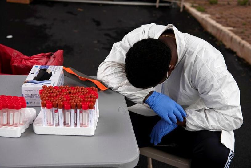 Nhân viên y tế nghỉ mệt vì thời tiết quá nóng trong khi hàng dài ôtô xếp hàng chờ xét nghiệm COVID-19 ở bang Texas, Mỹ ngày 7-7-2020 - Ảnh: REUTERS