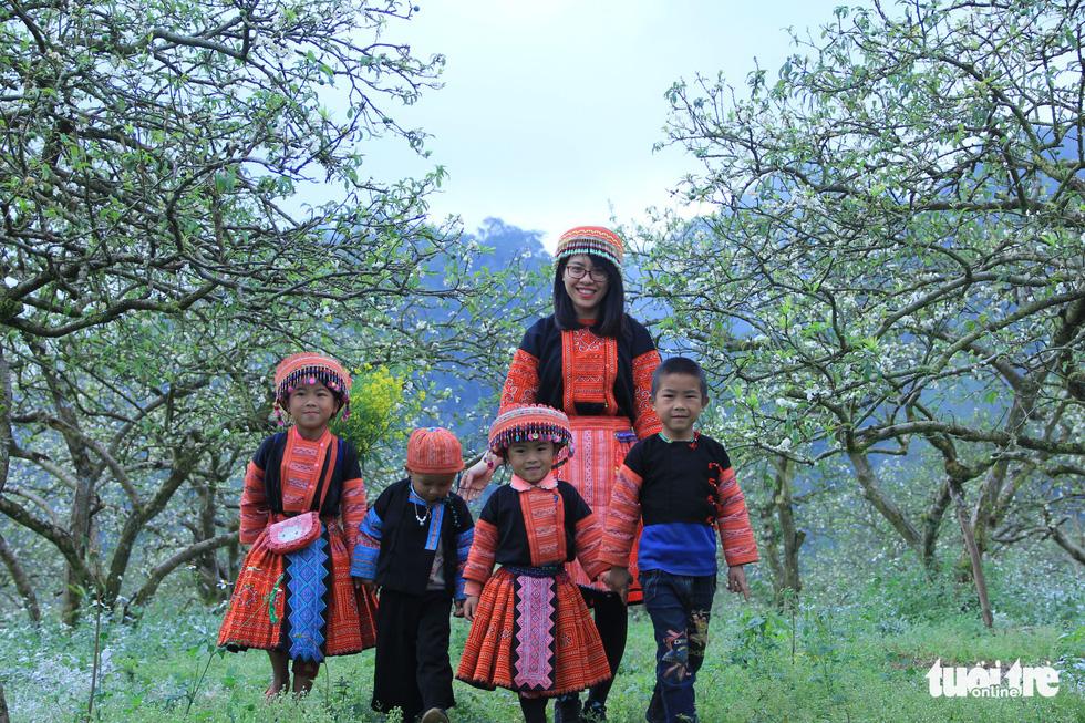 Hoa mận bung nở, thiếu nữ, trẻ em xúng xính váy áo dân tộc Mông đi giữa rừng mận đẹp như bức tranh vẽ