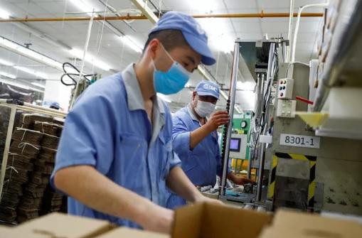 Nhân viên đeo khẩu trang làm việc tại một nhà máy của Công ty SMC (Nhật Bản) ở thủ đô Bắc Kinh - Trung Quốc hồi tháng 5-2020 Ảnh: REUTERS