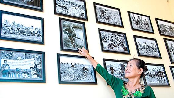 Chị Lâm Hồng Đẹp xem lại ảnh chân dung mình tại triển lãm.