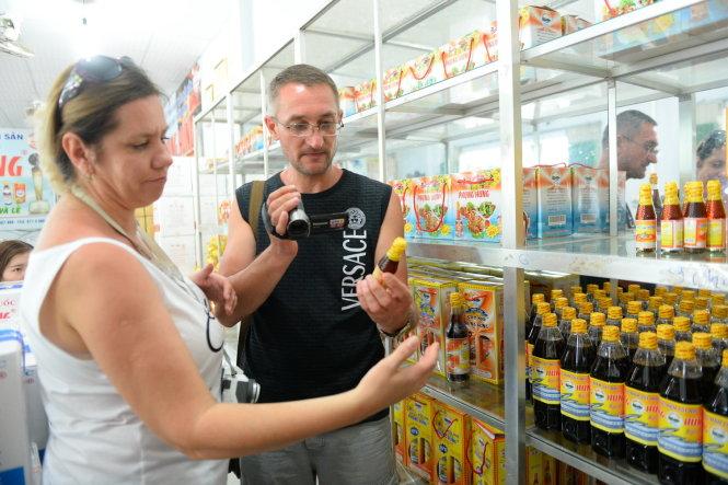 Khách nước ngoài chọn mua nước mắm truyền thống Phú Quốc - Ảnh: HỮU KHOA