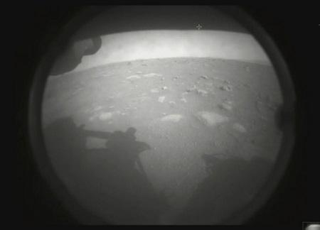 Tàu Perseverance gửi về những hình ảnh đen trắng từ bề mặt sao Hỏa, cho thấy bóng của con tàu đổ trên bãi đá hoang vắng mà nó đáp xuống - Ảnh: Twitter